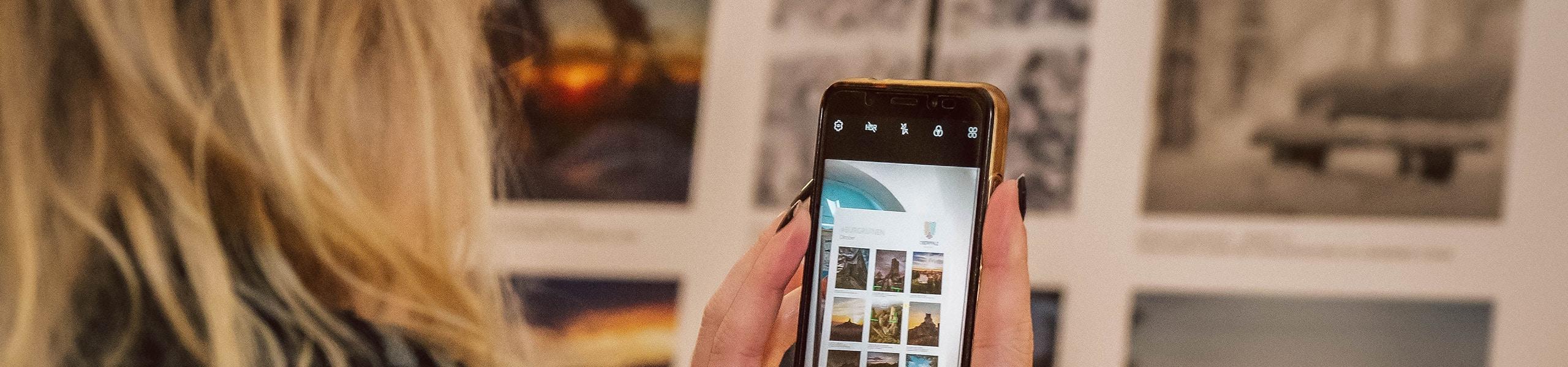 Besucherin fotografiert die Ausstellung #meineoberpfalz mit ihrem Handy