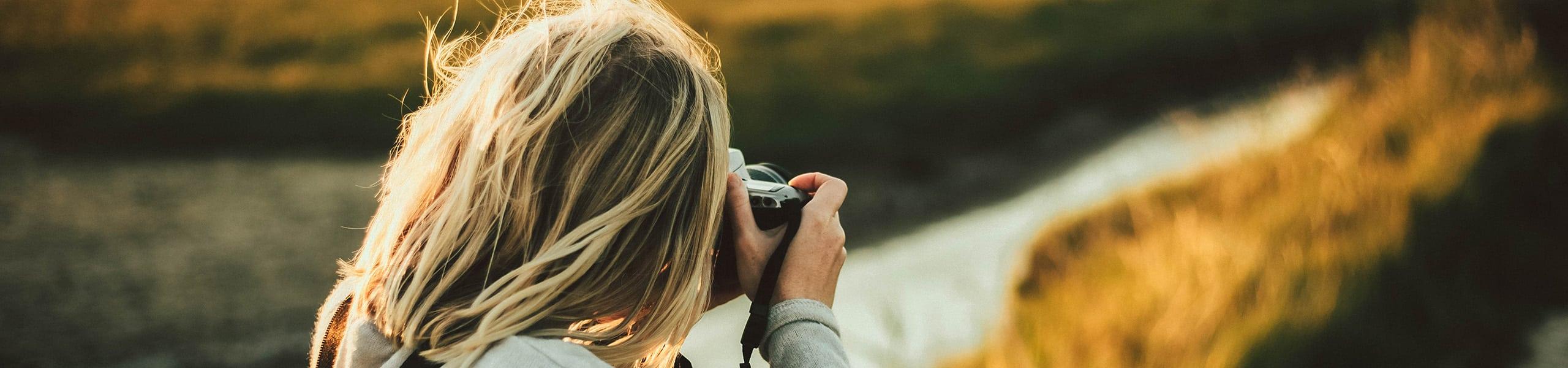 Frau fotografiert eine Landschaft