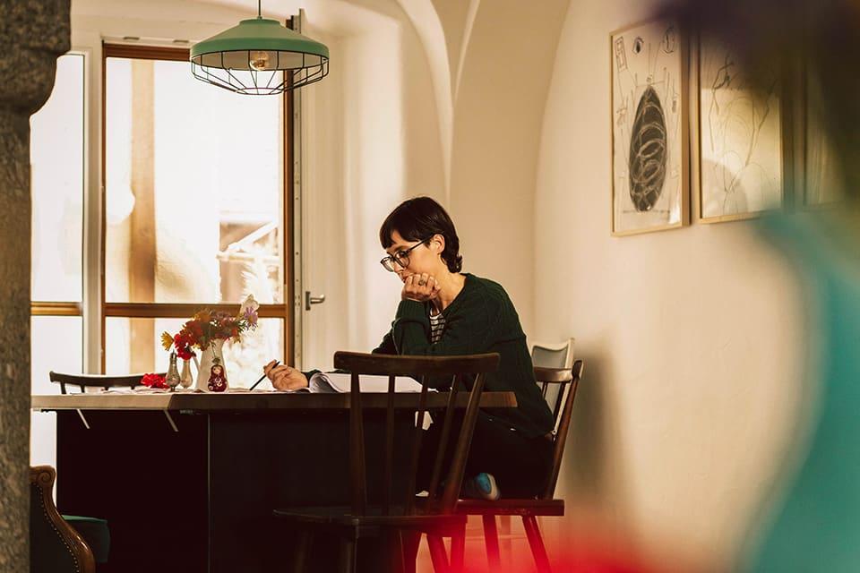 Kabarettistin Eva Karl-Faltermeier sitzt am Tisch