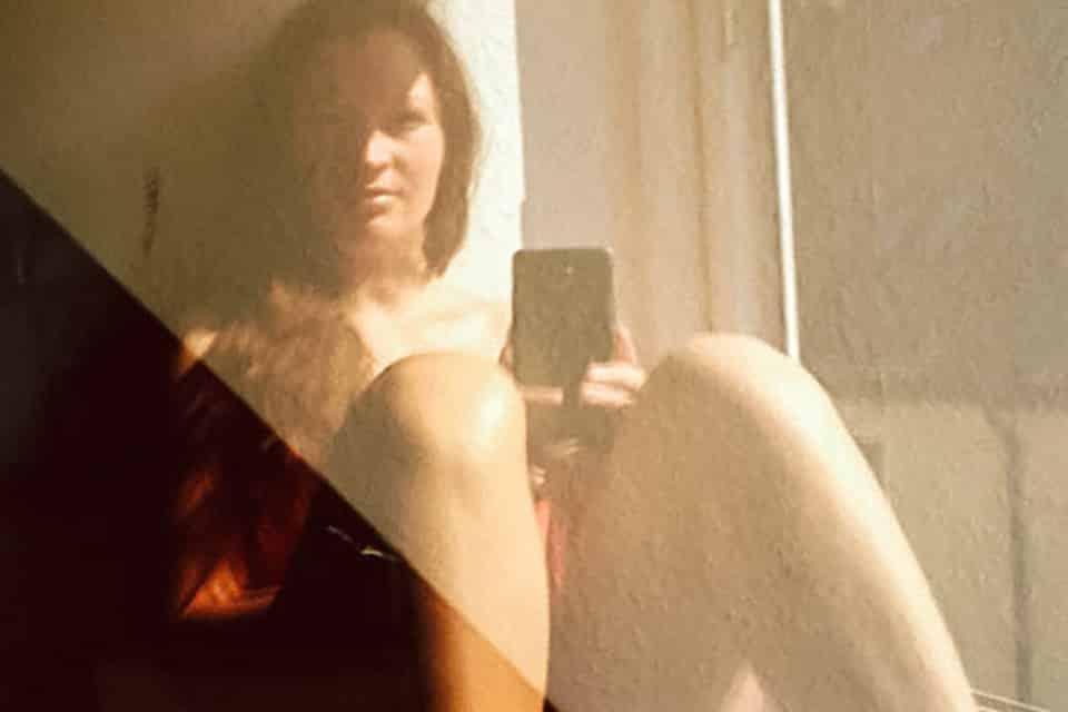 Maria Rammelmeier spiegelt sich in einer Fensterscheibe