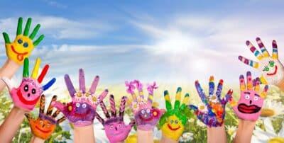 Hnde spielender Kinder vor Blumenwiese