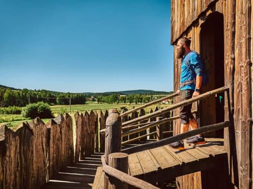 Ein Mann steht vor einer Hütte im Geschichtspark Bärnau-Tachov